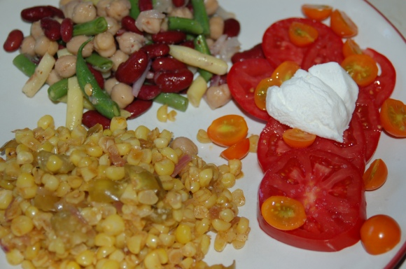 Tomatillo-corn sauté, three bean salad and sliced tomatoes with goat cheese.